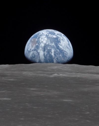 Questa vista dalla navicella Apollo 11 mostra la Terra che sorge sopra l'orizzonte della luna. Il terreno lunare nella foto si trova nella zona di Smyth's Sea sul lato vicino. Immagine Nasa 16-24 luglio 1969